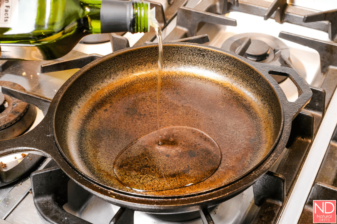 picture of cast iron skillet with oil being poured in