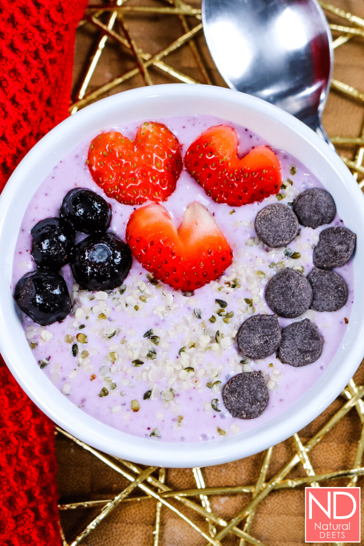 purple colored yogurt in a white bowl topped with blueberries, heart straweberries, chocolate chips and hemp hearts