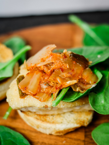 a bottom hamburger bun, pan fried chicken patty and topped with spinach and kimchi