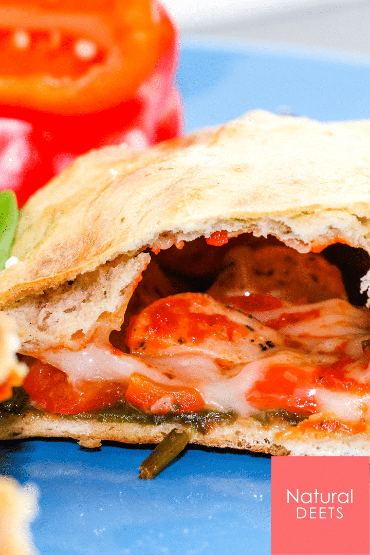 picture of a calzone cut in half so you can see the cheese, meat and pizza sauce oozing out