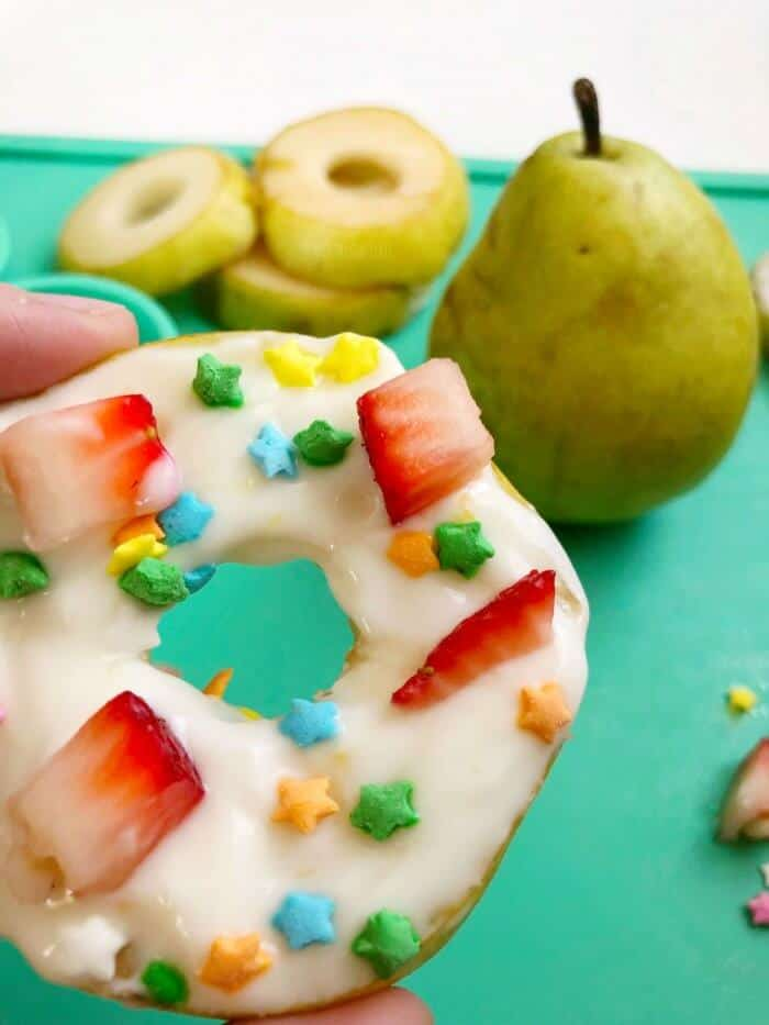 a picture of a pear slice with the middle out in the shape of a donut. covered with white yogurt and sprinkles