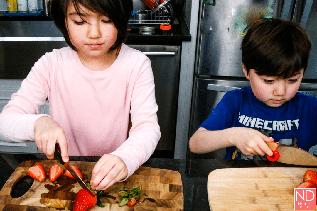 two children chopping cutting strawberries on their own boards
