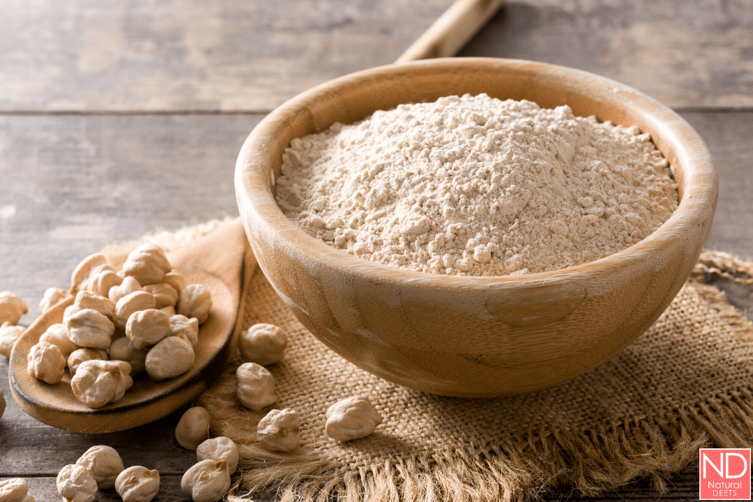 picture of garbanzo bean flour in a bowl with garbanzo beans on a wooden spoon