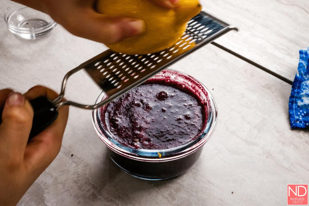 a hand zesting a lemon over a bowl of jam