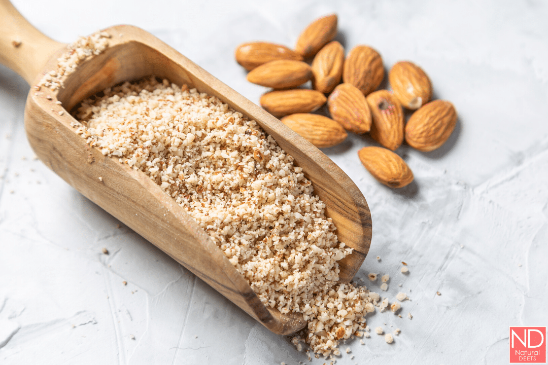 a picture of almond flour in a wooden spoon with almonds around it