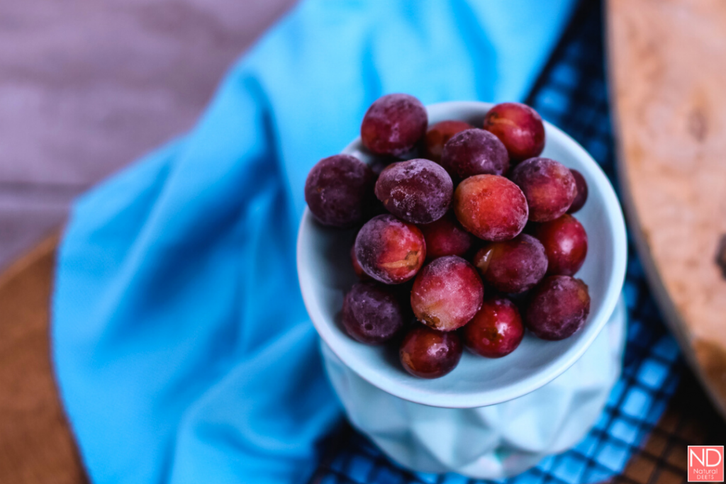grapes on a light blue plate iwth a bright blue napkin and cutting board in the background