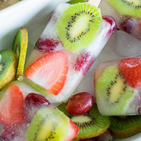 kiwi and strawberry slices in a coconut water popsicle