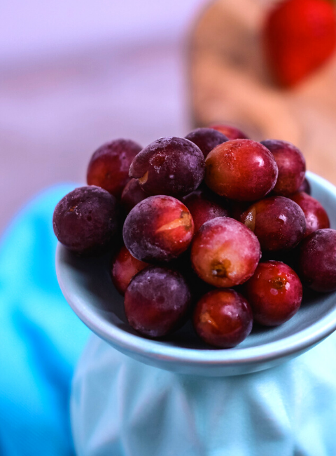 frozen grapes on a light blue platter with a bright blue napkin in the background