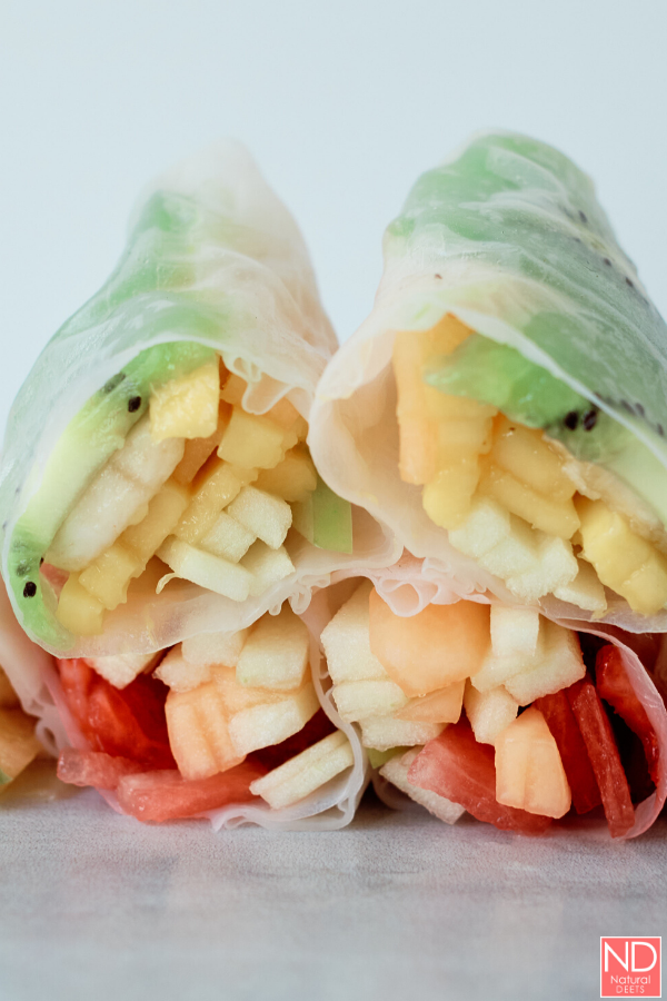 fruit spring rolls cut in half to show the layers of fruit