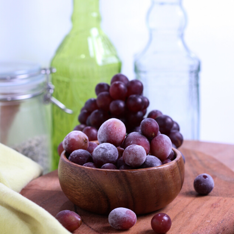frosted grapes in a wooden bowl on a cutting board