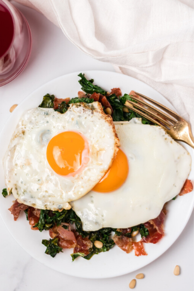 top view of the sauteed kale and proscuitto with two fried eggs on top