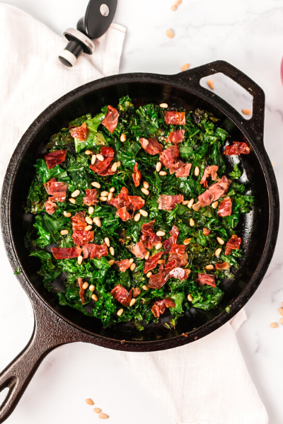 top view of a cash iron skillet with sauteed kale and prosciutto