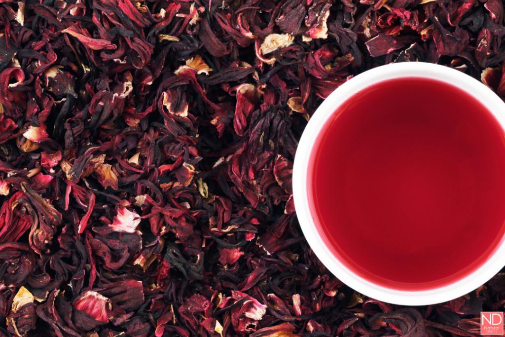 cup of hibiscus tea among hibiscus tea leaves