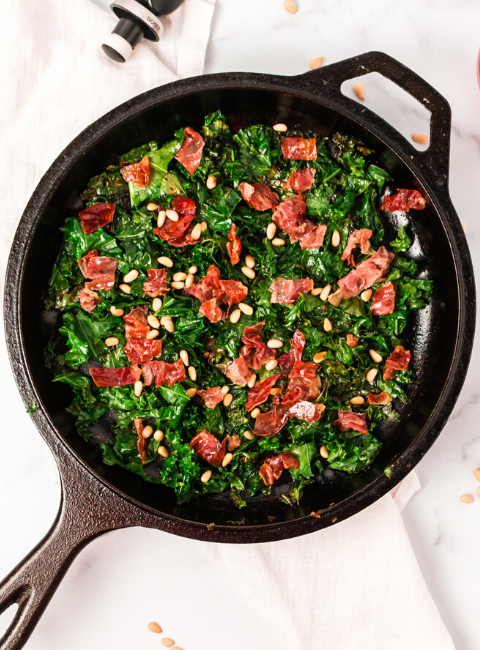top down view of the kale and prosciutto in a cast iron pan
