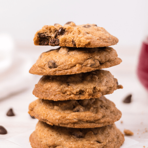 a stack of 5 chocolate chip cookies and the top one has a bite