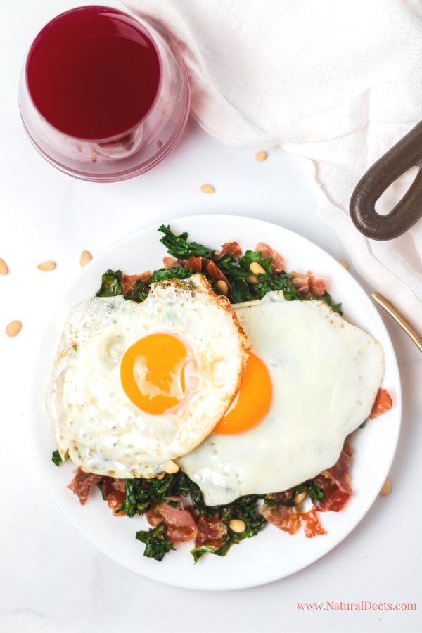 a fried egg on top of a plate of prosciutto and kale with a red drink and the handle of the cast iron pot in the corner