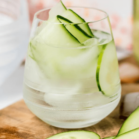 side view of a glass with water, ice and cucumber ribbons