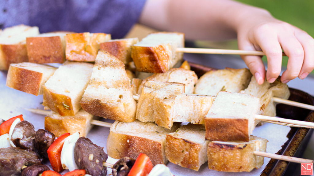 picture of bread skewers and a little kid hand grabbing one