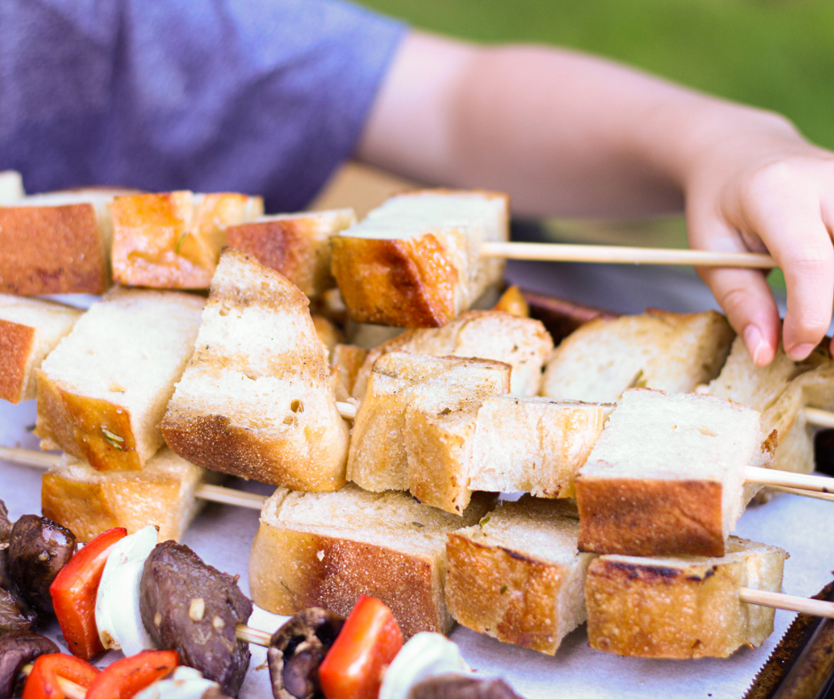 breads on skewers with a kid hand grabbing one