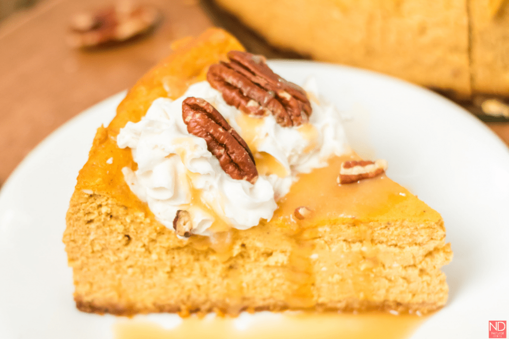 slice of cheesecake on a plate with whipped cream, caramel and pecans