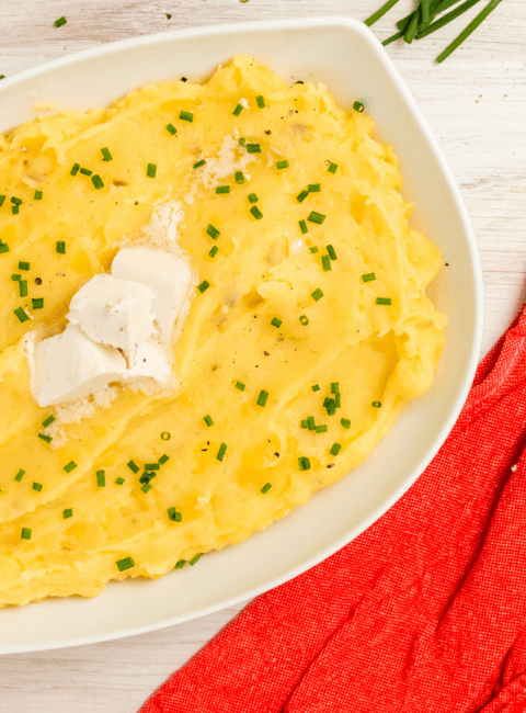 yellow mashed potatoes in a white bowl on an orange towel