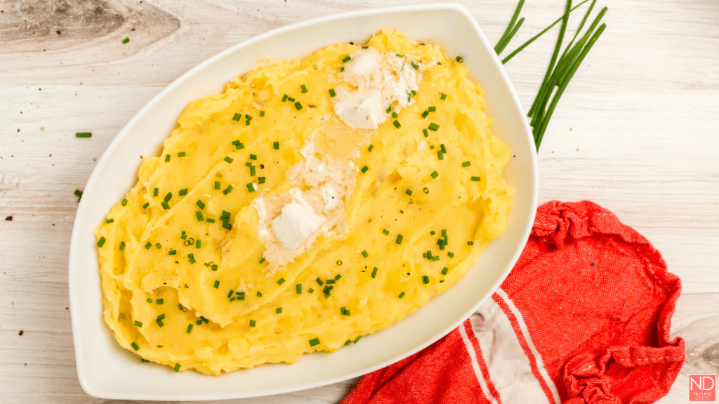 yellow mashed potatoes in a white serving dish with melted butter on the top