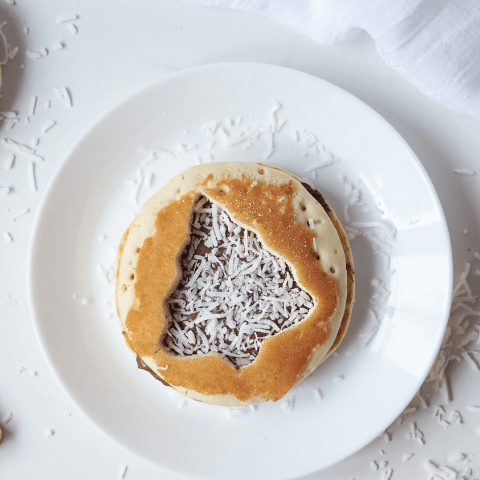 top view of a brown pancake with a christmas tree cut out and sprinkled with white shredded coconut