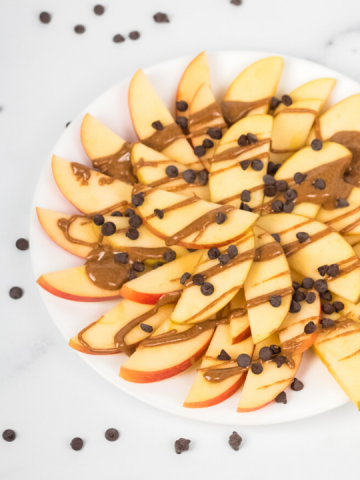 top view of a plate of apple nachos with chocolate chips and nut butter
