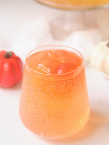 a stemless wine glass with orange colored juice and an orange pumpkin ice cube