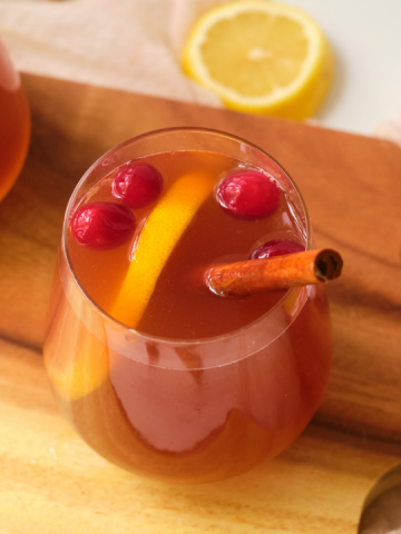 a side view of a stemless wine glass with cloudy apple juice and garnished iwtwh an orange slice and cinnamon stick