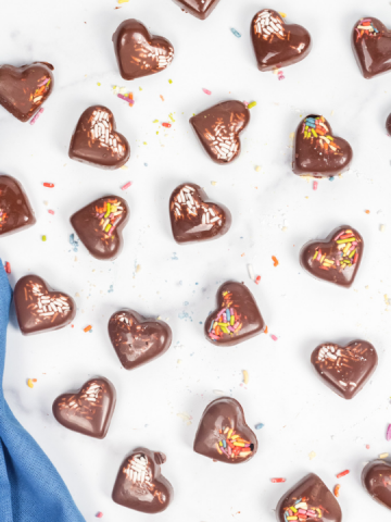 top view of chocolate hearts with sprinkles on a granite background