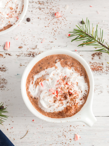 top view of peppermint hot chocolate in a white mug with whipped cream and crushed candy canes