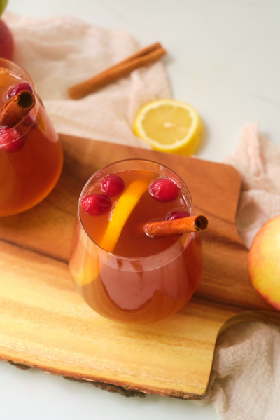 a top view of a stemless wineglass with apple cider colored liquid and garnished with a lemon lice, cranberries and a cinnamon stick
