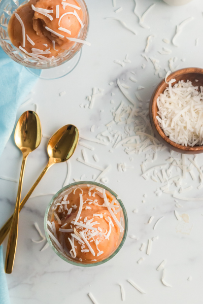 top view of two bowls of pink nice cream in glass bowls with a brown bowl with shredded coconut and two gold spoons