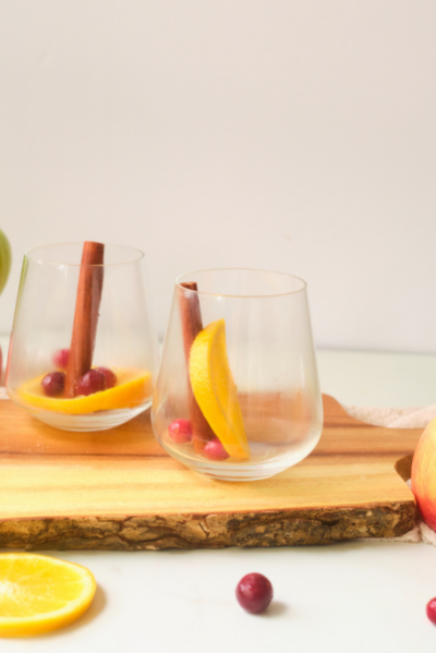 side view of an empty stemless wine glass with a cinnamon stick, orange slice and a few cranberries