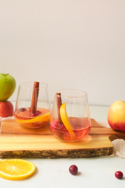 stemless wine glass with about 1 inch of pink rose wine with a cinnamon stick, orange slice and cranberries