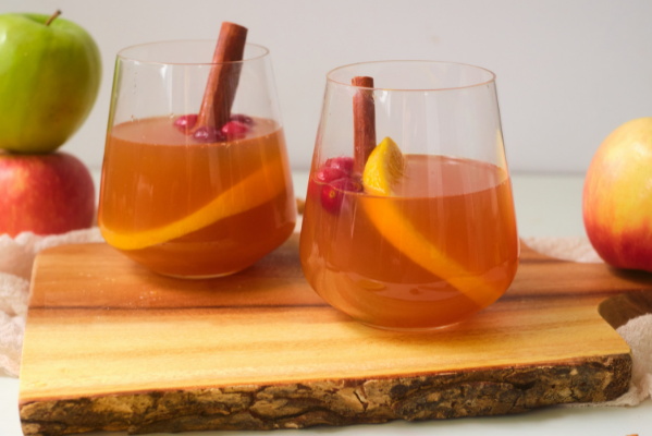 side view of two wine glasses on a wood tray. Glasses filled with cloudy apple juice and have an orange peel showing through the glass