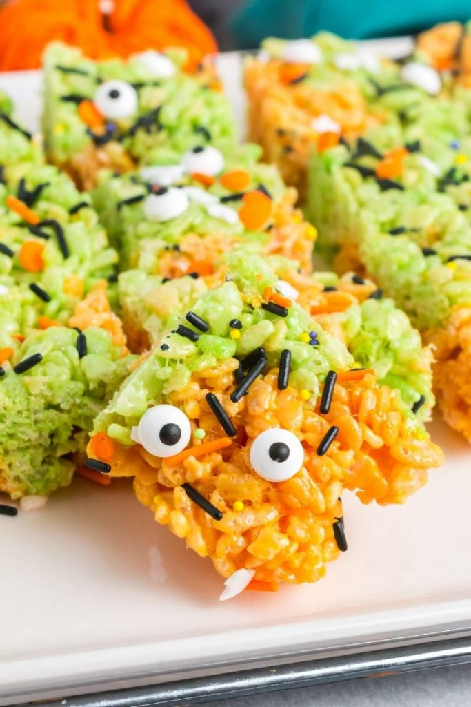 45 degree view of a quare of orange and green swirled rice krispie treats with two candy eye balls