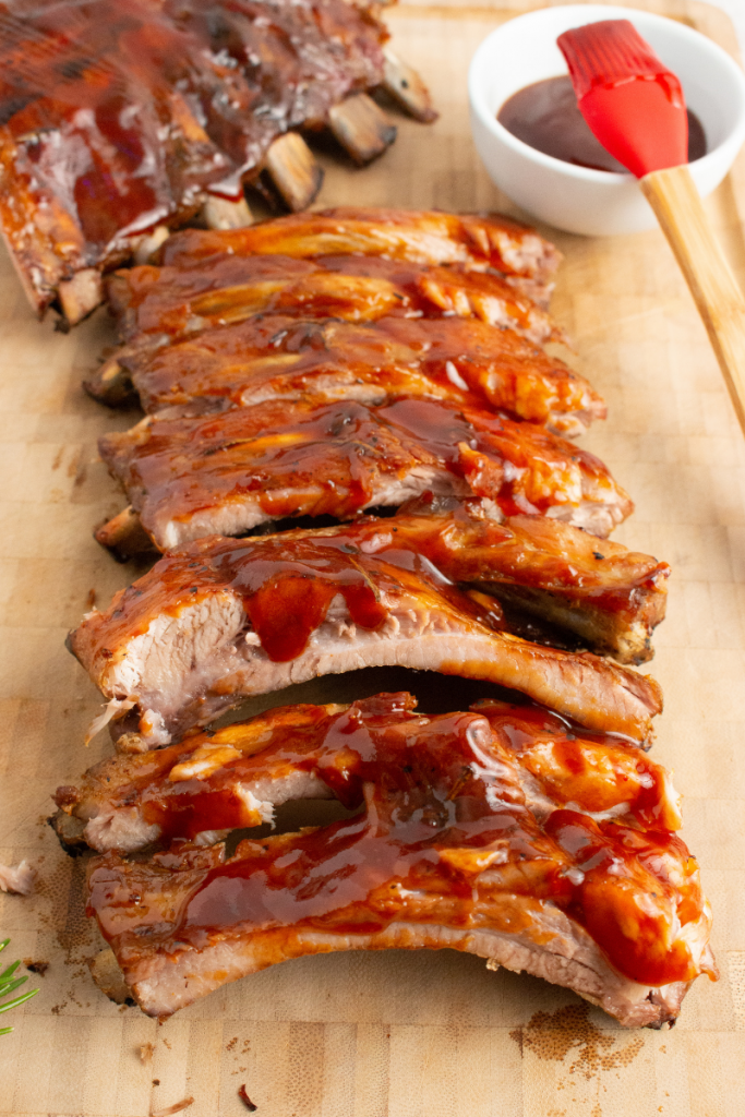 side view of ribs cut up and lined up on a wooden cutting board