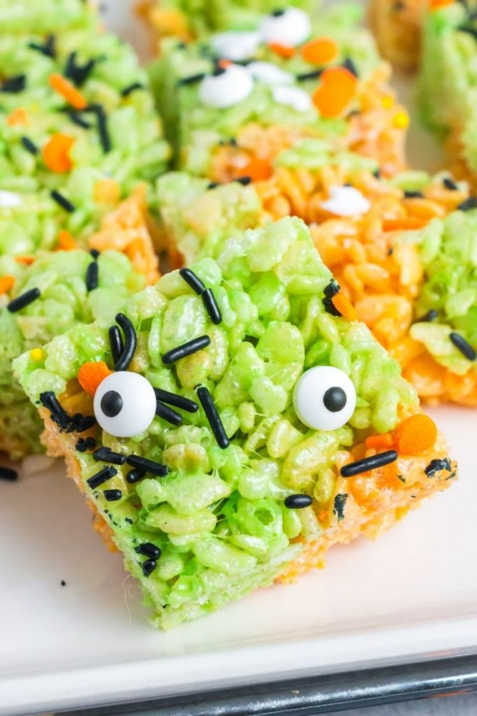 green and orange rice krispy square with black and orange sprinkles and two eye ball candies