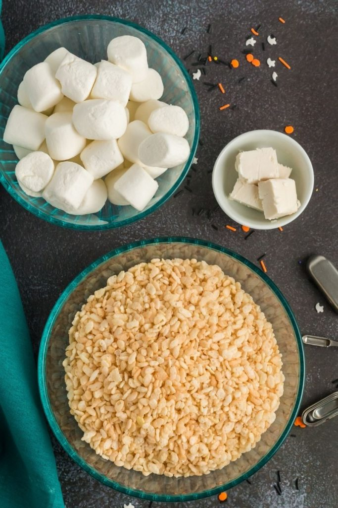 top view of a bowl of rice krispies, a bowl of marshmallows and a bowl of butter