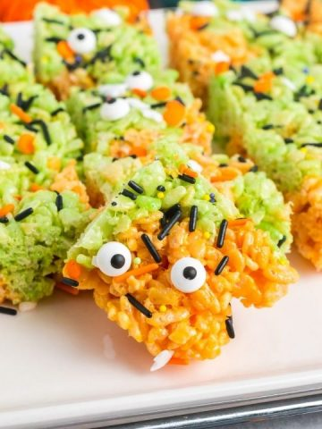 side view of a orange and green rice crispy treat with candy eyes and spirnkles