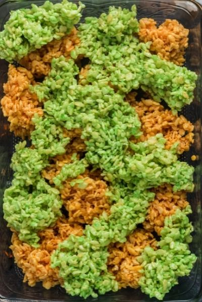 top view of a pan with green and orange rice krispy treats