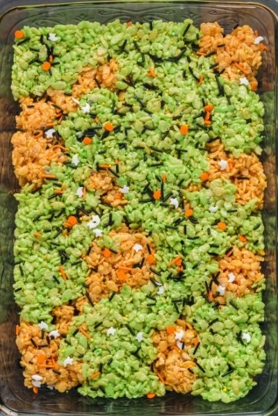 top view of green and orange rice krispy treats pressed into in a pan and spirnkled with white ghots, orange pumpkins and black sprinkles
