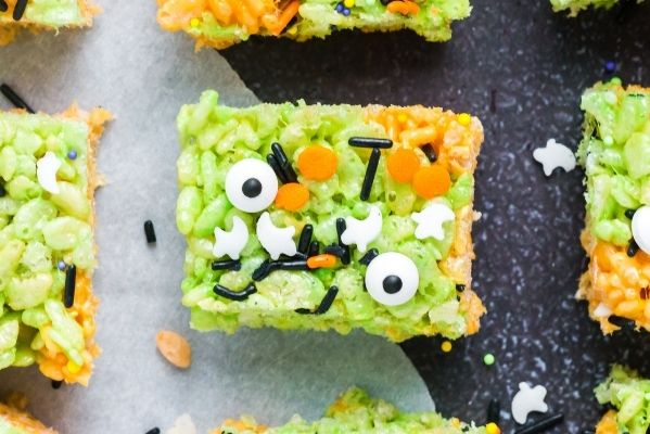 a top view of a rice crispy square that is mostly green with orange and black sprinkles and two candy eye balls